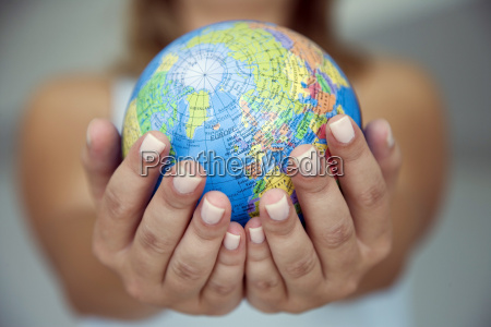 womans hands holding world globe