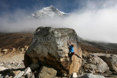 a climber tackles a difficult boulder
