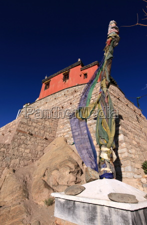 a stupa bound with prayer flags