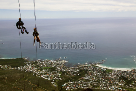 abseilers descend cliffs on table mountain