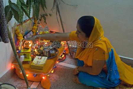 sikh woman placing deepak light on