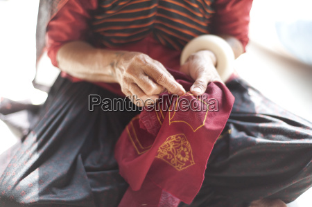 aahir tribeswoman embroidering intricate traditional patterns