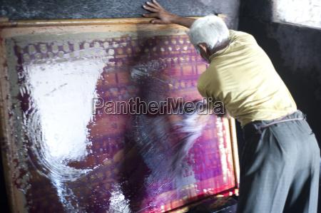 man washing ink off screen used