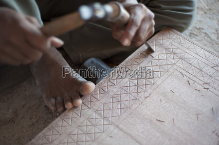 carpenter chiselling traditional pattern in a