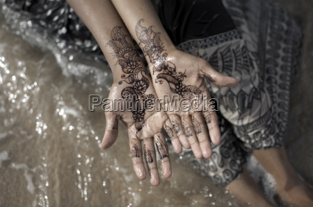 henna adorn the hands of a