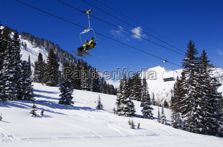 a chair lift carries skiers at