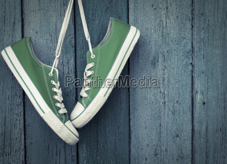 green youth sneakers hanging on a