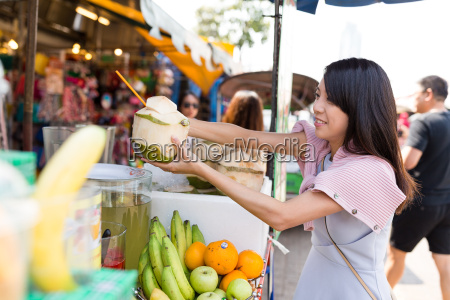 woman buying coconut drink in weekend