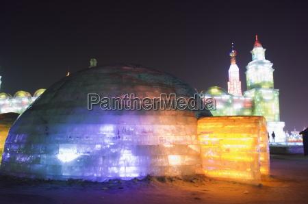 an igloo ice sculpture illuminated at