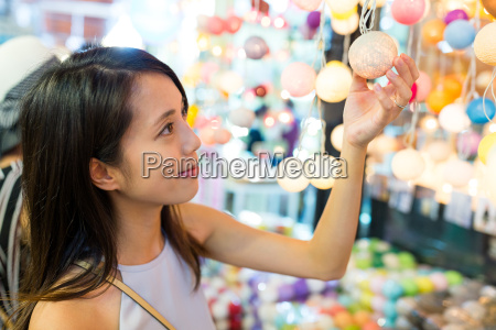 woman buying lantern in weekend market