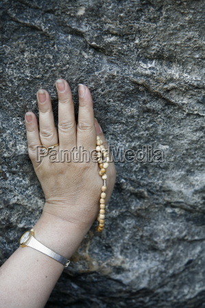pilgrim touching the lourdes grotto lourdes