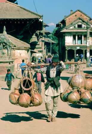 man carrying heavy pots on shoulder