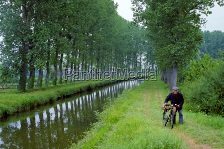 a man walking beside a canal