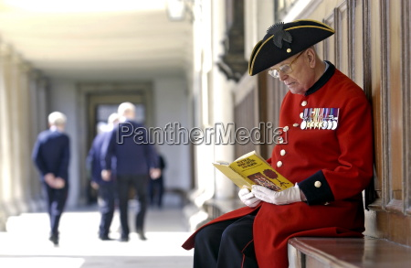 a chelsea pensioner sitting outside the