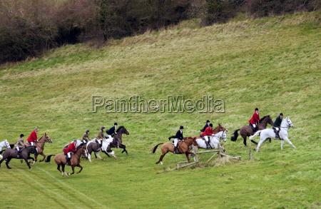 huntsmen riding across fields during the