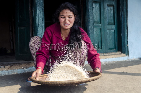 a woman sifts rice to remove