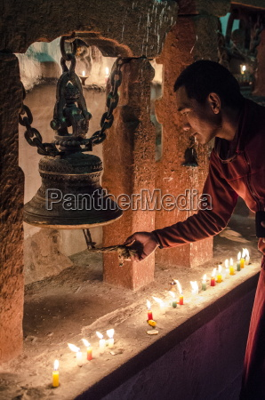 a buddhist monk rings a prayer