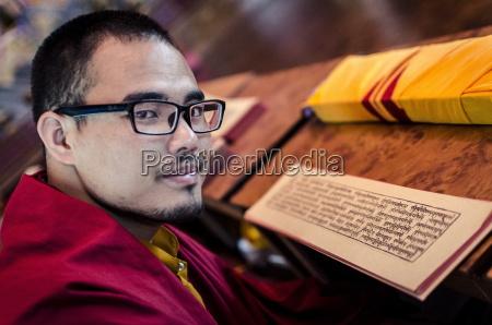 a buddhist monk reads a volume