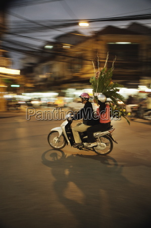 couple on moped carrying floral display