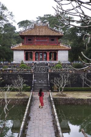 vietnamese schoolgirl walking over bridge to