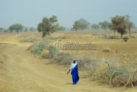 a veiled native woman walking alone
