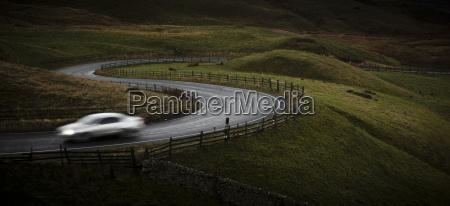 silver sports car driving through winding
