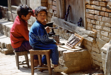 young child workers painting carvings bhaktapur