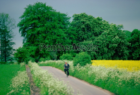 man cycling along country lane near