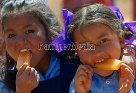 nepalese girls possibly sisters enjoying orange