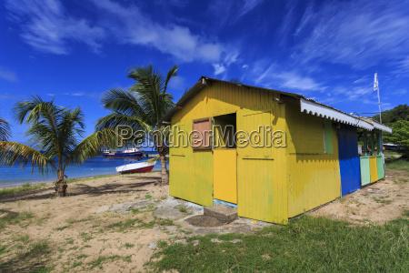 colourful beach hut bar and boats