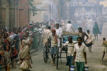 rickshaws pass as poor people queue