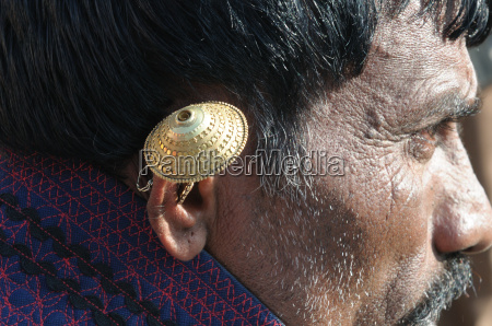 gold ear ring worn by a