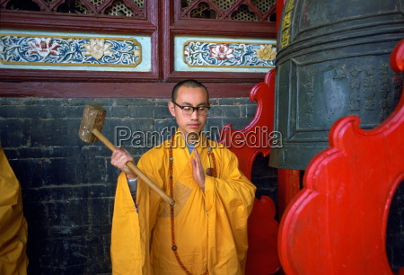buddist monk ringing the huating temple