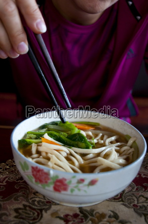 woman eating noodle soup lhasa tibet