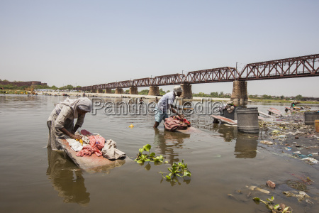 women wash clothes in the polluted