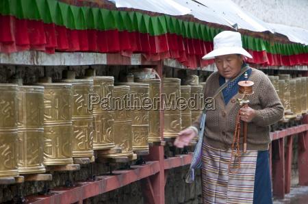 old woman walking along the praying