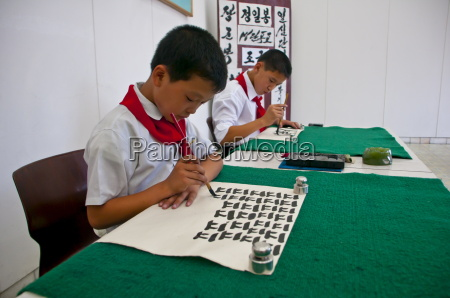 young boys practising calligraphy in the