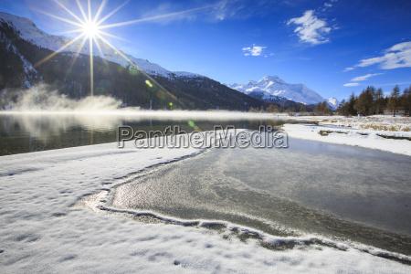 rays of winter sun illuminate lake
