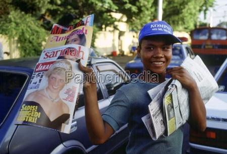 boy sells magazines in jakarta that