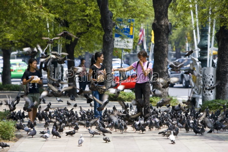 women sell bags of bird seed