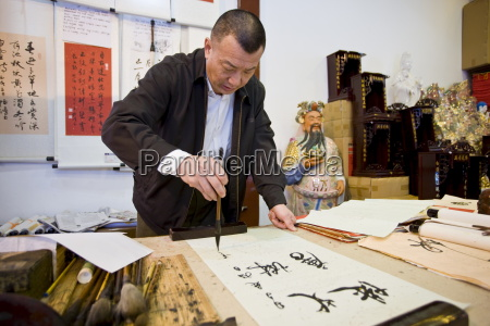 skilled chinese calligrapher at work in