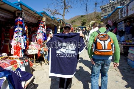tourists walk past souvenir tee shirt