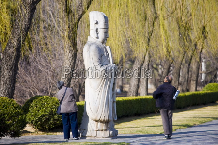 elderly tourists look at statue of