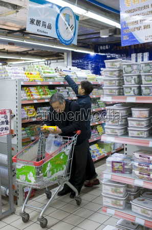 man with shopping trolley reading product