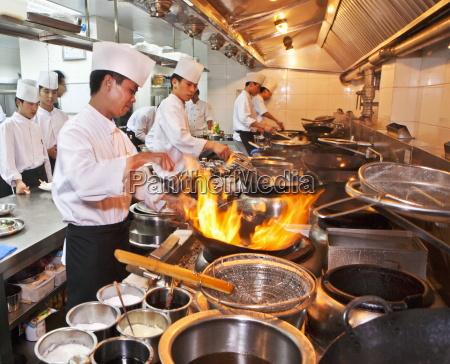 chefs preparing chinese cuisine in woks