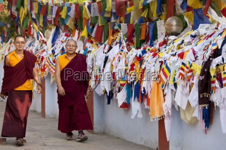 buddhist monks pass prayer flags at