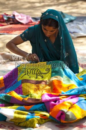 indian woman sewing textiles at dastkar