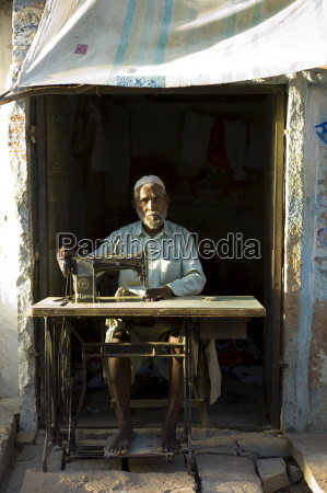 indian man with sewing machine in
