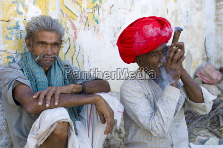 indian man in traditional clothing smokes