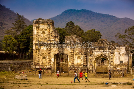 kids playing soccer at ruins in